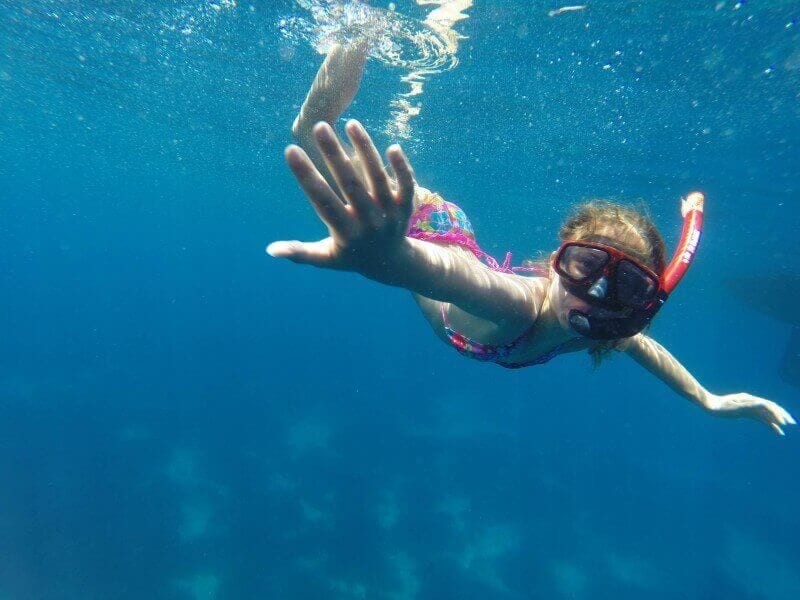 girl under the water with a snorkel on a yacht charter in greece