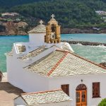 view of a church and the ocean on the island of Skopelos on a greek islands catamaran charter