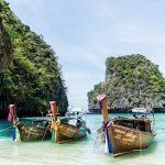 boats on a thailand yacht charter in Phuket with limestone mountains