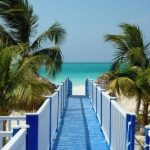 view of a bridge and white sand with palm trees on a cuba yacht charter