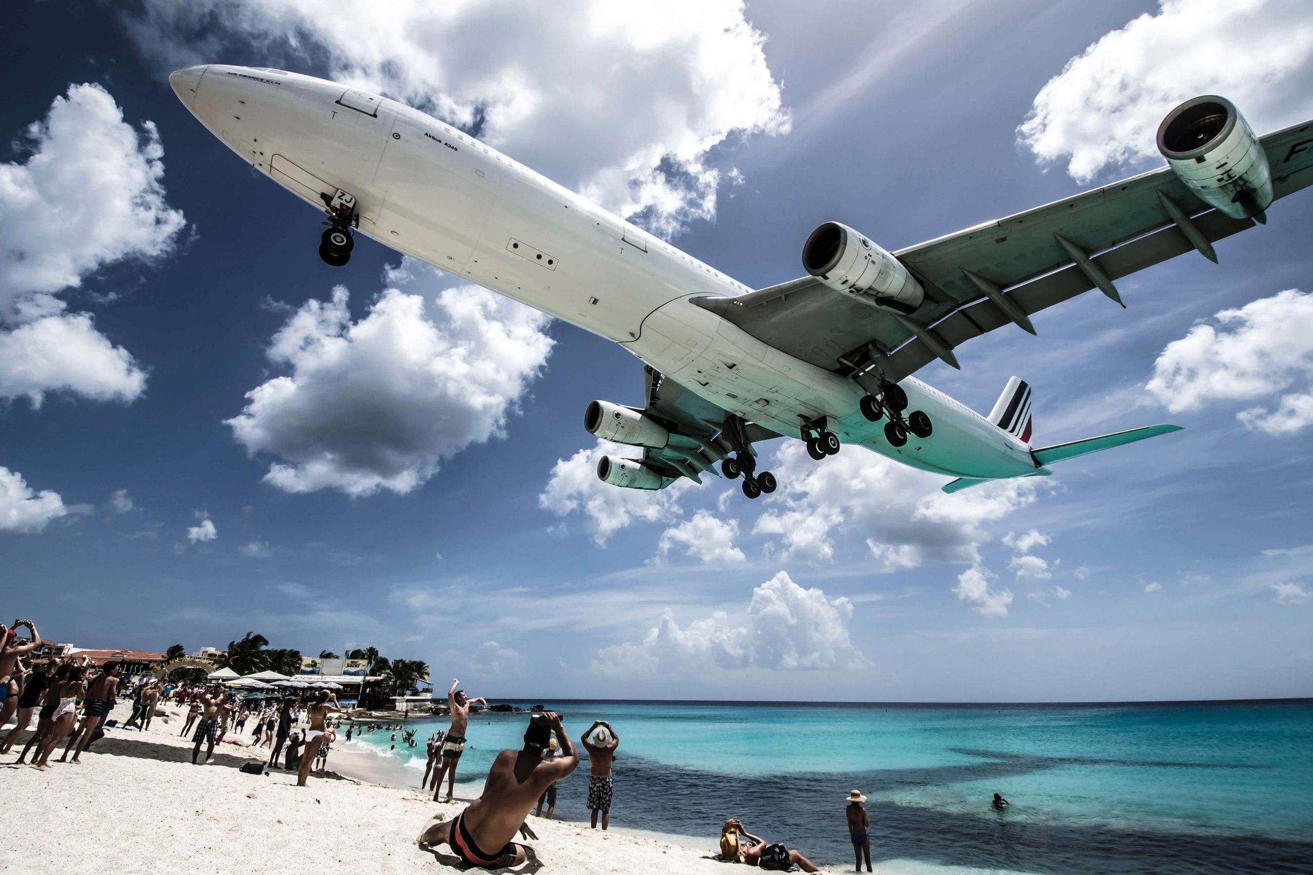 plane flying over a beach close to airport in st Maarten